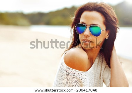 Fashionable brunette woman portrait in sunglasses - closeup  - stock photo