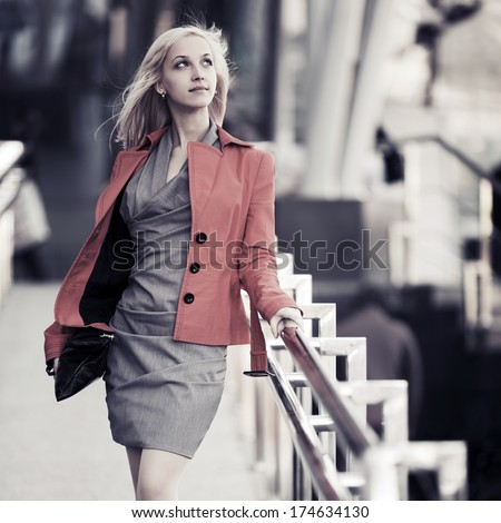 Fashionable business woman walking on the city street - stock photo