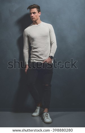 Fashionable casual young man wearing beige sweater and black jeans. Standing against gray wall. - stock photo