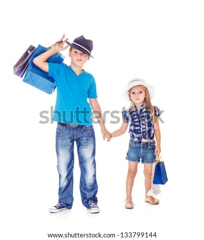 Fashionable children holding hands and shopping bags - stock photo