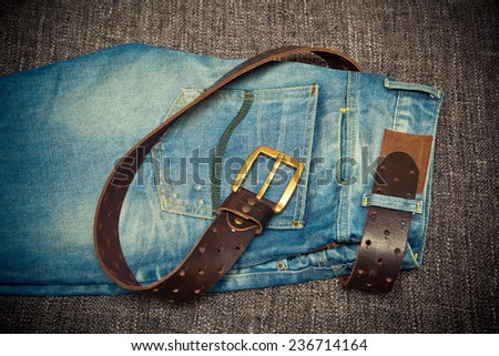 Fashionable clothes: blue jeans and leather belt with buckle  - stock photo