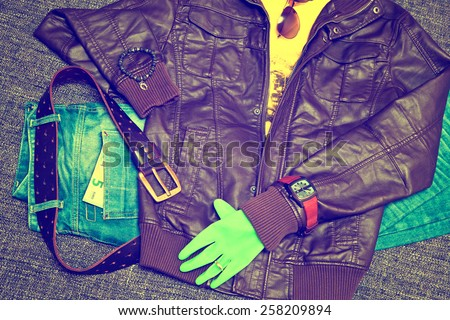 Fashionable clothes: blue jeans with a leather belt, leather jacket, T-shirt, watches, sunglasses, bracelet on the arm, glove, 5 Euro banknote - stock photo