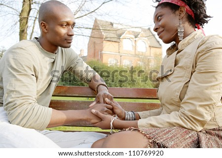 Fashionable couple holding hands while sitting on a wooden bench in a park in the city.