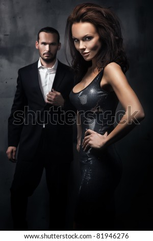 Fashionable couple in a dark room - stock photo