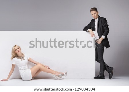 Fashionable couple next to a white board