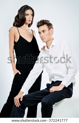 Fashionable couple posing at studio. Isolated over white.