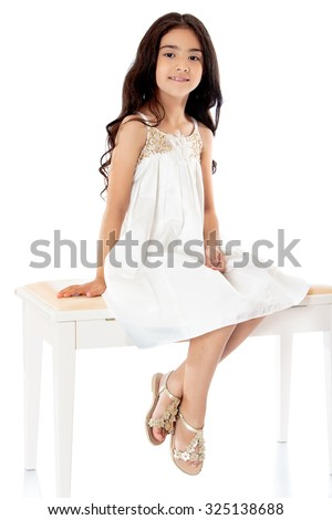 Fashionable dark-haired little girl in a beautiful beige dress sitting on white couch with his feet dangling. -Isolated on white background - stock photo