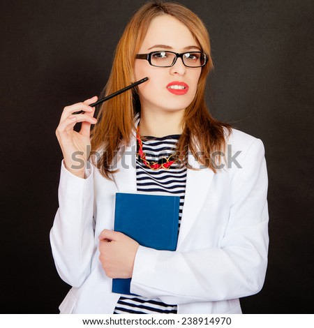 Fashionable doctor. Confident young female doctor in white uniform and glasses holding book and pencil while standing against black background - stock photo