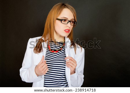 Fashionable doctor. Confident young female doctor in white uniform and glasses looking away while standing against black background - stock photo