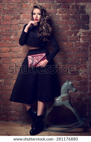 Fashionable dressed girl standing near red brick wall and blue wooden toy horse. Pretty woman wearing black costume of long dress and jacket and holding red handbag. - stock photo