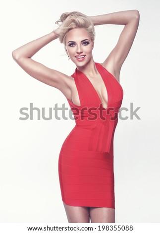 Fashionable elegant blonde woman posing in red dress, smiling. - stock photo