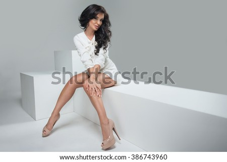 Fashionable elegant brunette woman posing in dress, looking at camera, smiling.