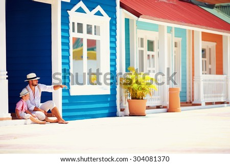 fashionable father and son sitting and talking on caribbean street - stock photo