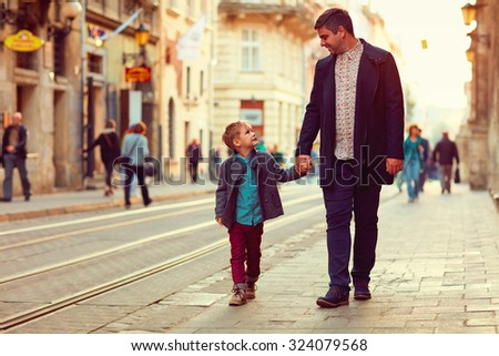 fashionable father and son walking in old city street - stock photo