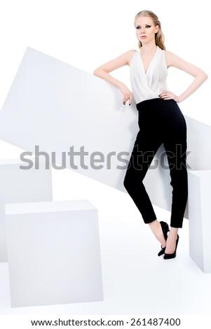 Fashionable female model posing at studio. Beauty, fashion photo. Clothing. Body care. Isolated over white. - stock photo