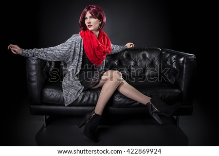 Fashionable female sitting and resting on a comfortable black leather couch.  The image depicts luxury.