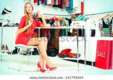 Fashionable girl choosing shoes in a store. - stock photo
