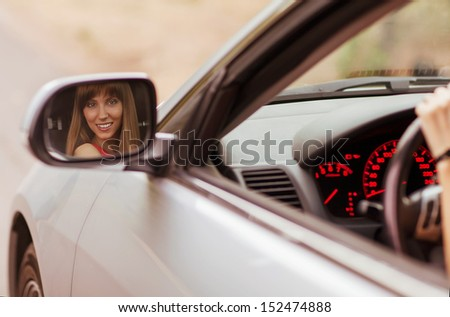 Fashionable girl sitting in a gray car. Her smiling face reflected in the side mirror. - stock photo