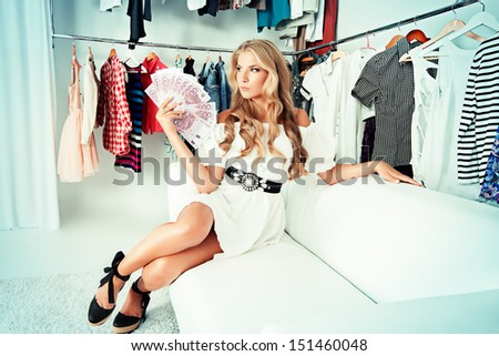 Fashionable girl sitting with a bundle of money in a store. Shopping. - stock photo