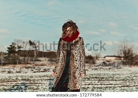 Fashionable girl with dreadlocks in leopard coat for winter field - stock photo