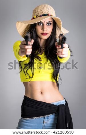 Fashionable girl with guns isolated on grey background - stock photo