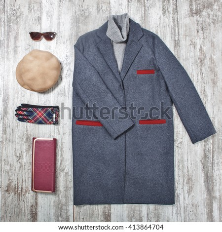 fashionable gray coat with fashion accessories on wooden surface top view - stock photo