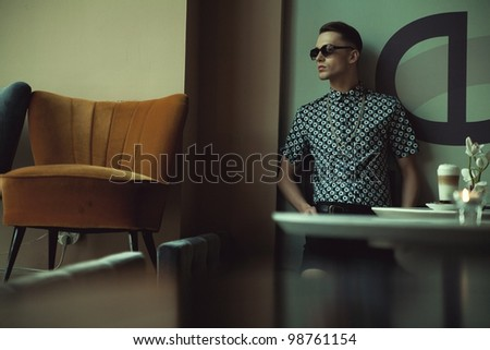 Fashionable guy in a stylish interior - stock photo