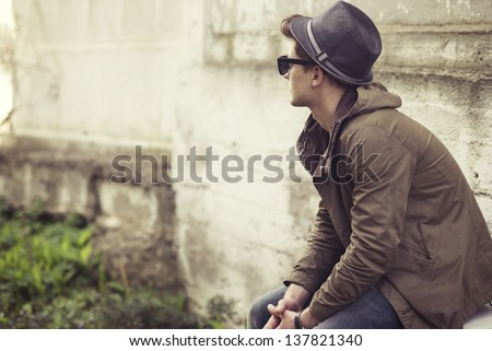 Fashionable guy sitting on a background of an old wall - stock photo
