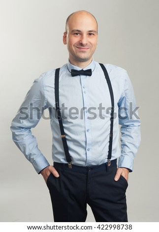 fashionable handsome bald man in suspenders and butterfly tie smiling and looking at camera - stock photo