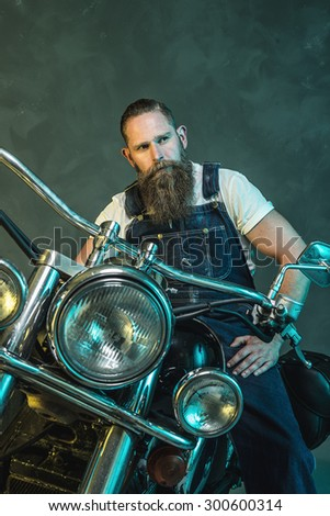 Fashionable Handsome Bearded Man in Denim Jumpsuit Sitting on his Motorcycle and Looking Into the Distance Against Smoky Wall Background. - stock photo