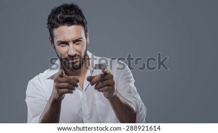 Fashionable handsome man pointing at camera with strong attitude - stock photo