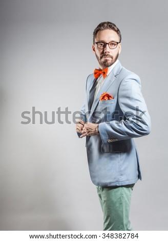 Fashionable handsome stylish bearded man in light blue blazer, orange bowtie and  handkerchief - stock photo