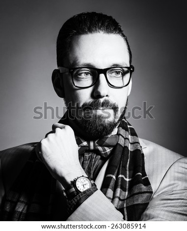 Fashionable handsome stylish bearded man with glasses and in a checkered scarf and bow tie. - stock photo