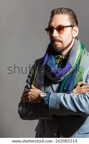 Fashionable handsome stylish bearded man with sunglasses and in a checkered scarf and bow tie. - stock photo