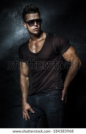 Fashionable handsome young man posing in studio - stock photo