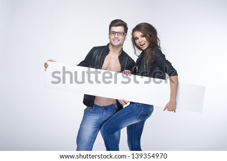 Fashionable happy pretty couple holding white board  - stock photo