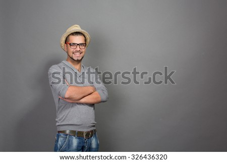 Fashionable hipster man posing with his arms crossed in studio. Smiling man in straw hat and glasses looking at the camera isolated in grey background. - stock photo