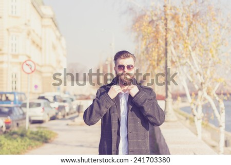 Fashionable Hipster style bearded man walking outdoor and get dressed. - stock photo