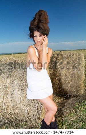 Fashionable image of a girl over farm background, portrait shot - stock photo