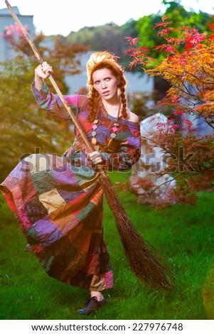 Fashionable in boho style girl holding broom - stock photo