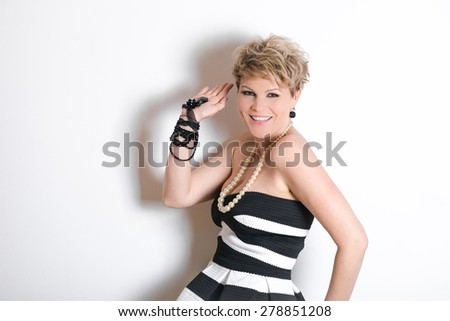 Fashionable lady in zebra dress posing near white brick wall. Beauty, fashion concept. blonde with short hair on a white background. a woman older than 30 years - stock photo