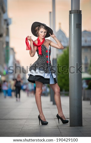 Fashionable lady wearing elegant dress, black hat and red scarf posing outdoor in urban scenery. Full length portrait of young beautiful elegant woman posing in summer city style. Street shot. - stock photo