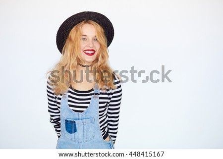 Fashionable lady with bright makeup in black and white shirt and jeans wearing a hat posing near white wall. Beauty, fashion concept.
