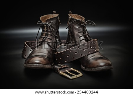 Fashionable leather men's shoes and leather belt with a buckle. Photo brutal clothes in dark style - stock photo