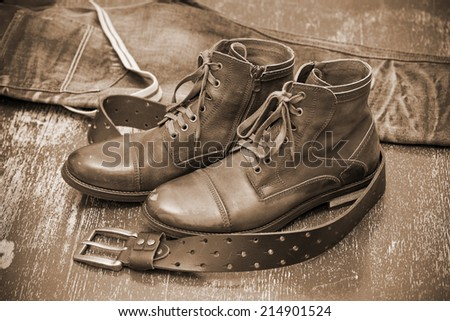 Fashionable leather shoes, leather belt and jeans. cowboy style. Autumn and spring shoes. Photo toning in sepia - stock photo
