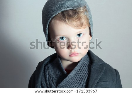 Fashionable Little Boy in Cap.Stylish Kid.Fashion Children.Handsome blond kid.Winter