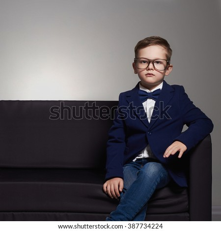 fashionable little boy in suit and glasses.stylish child on the chair - stock photo