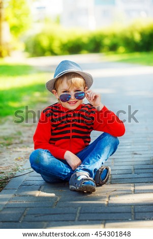 Fashionable little boy in sunglasses and cap  in sunny day. Childhood. Summertime. - stock photo