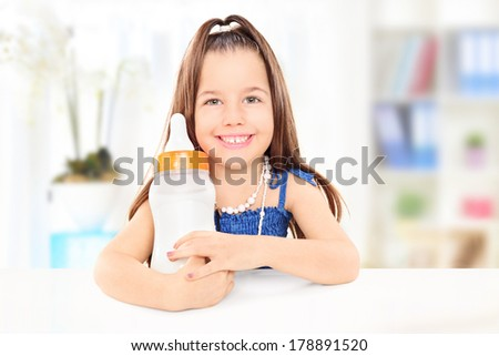 Fashionable little girl holding a baby bottle full of milk, at home - stock photo