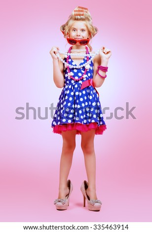 Fashionable little girl in her mother's hair curlers and pin-up sunglasses. Kid's fashion, cosmetics. Pin-up style. - stock photo